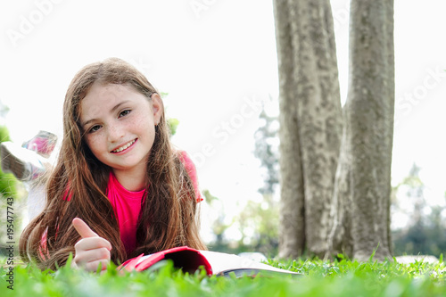 Child Girl Look And Smile Read Book Relax In Weekend Holiday