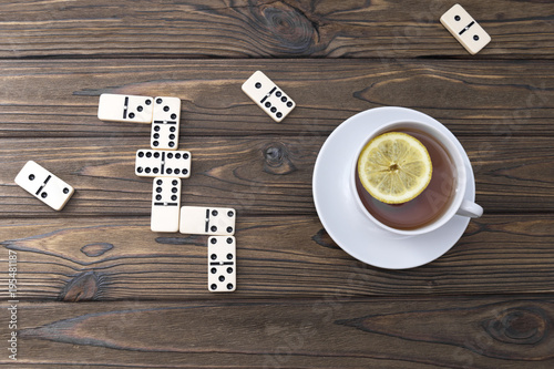 Foto op Plexiglas Chocolade a cup of tea with lemon, a domino on a wooden background. leisure. pastime.