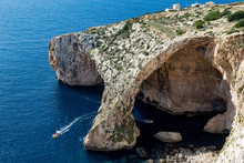 Boats Of Tourists Visiting The Dramatic Natural Arch At The Blue Grotto, Malta, Mediterranean