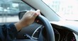 Commuter driving on road. Closeup of hands holding steering wheel