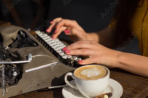 Fotografiet Female hands typing on retro typewriter