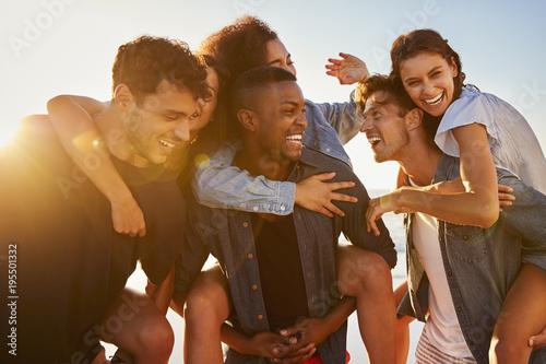 Obraz Group Of Friends On Vacation Having Piggyback Race On Beach - fototapety do salonu