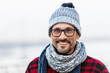 Portrait of smiling urban man in glasses and hat. Happy smiled guy in winter knitted hat and scarf. Smiled man in glasses on white background