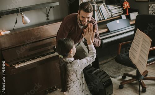 Cute little girl with guitar teacher in the room - 195506963