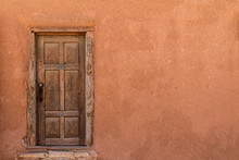 Rustic Wooden Door On Adobe Building Wall