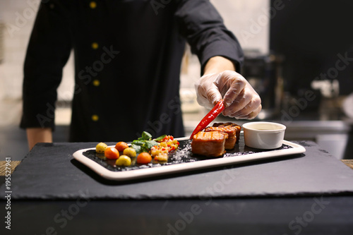 Chef preparing delicious grilled salmon wrapped in bacon and vegetable salsa for serving in restaurant