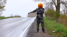 Poor Pumpkinhead Man Stand At Roadside With Written Sign 'get Me To Summer'
