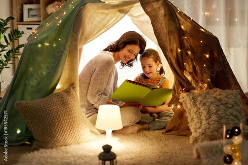 Plakaty do biblioteki happy-family-reading-book-in-kids-tent-at-home