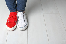 Woman In Different Sneakers Indoors