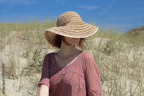 Woman With Empowered Personality Of Short Hair In Dark Brown Color Wearing Sun Hat Fashion Sitting On The Beach In Sunny Day And Blue Sky Relaxing And Enjoying Summer Buy This