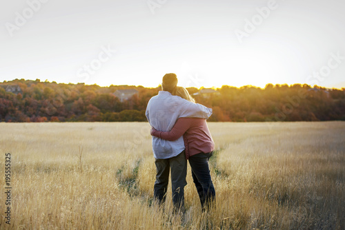 Photo loving adult couple hugging each other looking to the sunset horizontal