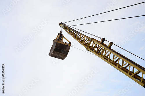 Fotografie, Tablou Old yellow mechanical clamshell grab on blue sky background