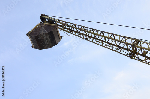 Photo  Old yellow mechanical clamshell grab on blue sky background