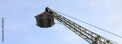 Fényképezés Old yellow mechanical clamshell grab on blue sky background