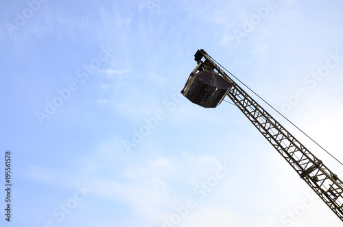 Fotografering  Old yellow mechanical clamshell grab on blue sky background