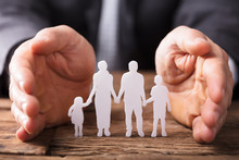 Businessperson's Hand Protecting Family Figures