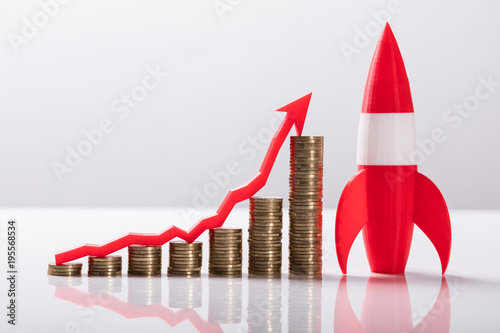 Fotografie, Obraz  Close-up Of Red Rocket Besides Stacked Coins And Arrow