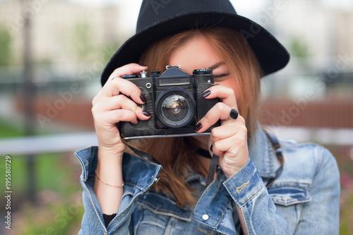 Fototapeta Young girl photographer walking along the street obraz na płótnie