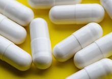 White Pill Capsule On Yellow B...