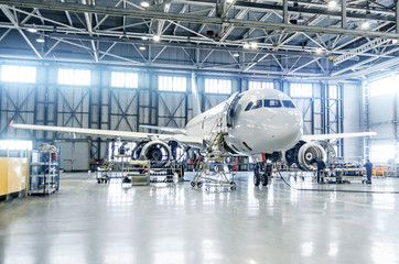 Passenger airplane on maintenance of engine and fuselage check repair in airport hangar.