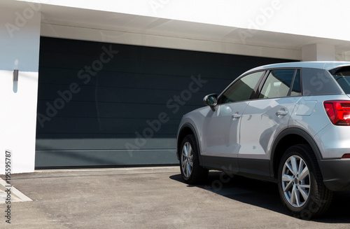Car in front of modern house waiting to enter in the garage with large garage do Poster Mural XXL
