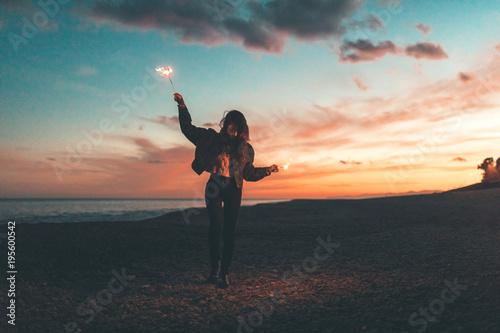 Ragazza con maglia bianca e giacca di jeans che balla sulla spiaggia al tramonto con le scintille nella mani