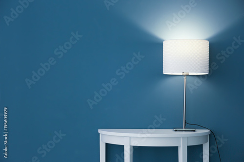 Photo Elegant lamp on table near color wall
