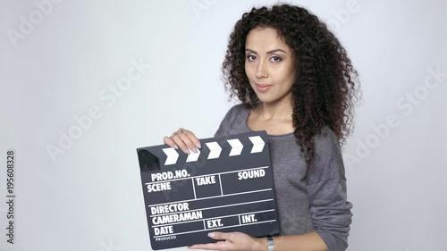 Smiling curly female holding movie clapper board, slate film. Wallpaper Mural