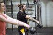 Man and woman exercising with kettlebell in gym