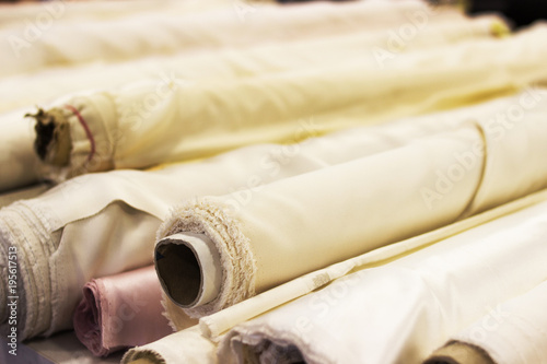 Poster Tissu Roll of white fabric for cutting. Rolls of light fabric