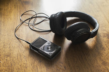 Mp3 Music Player With Headphone On Wooden Table