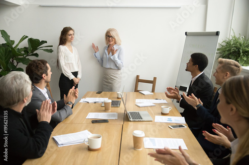Fotografía  Senior woman boss introducing new female worker making compliment for work resul