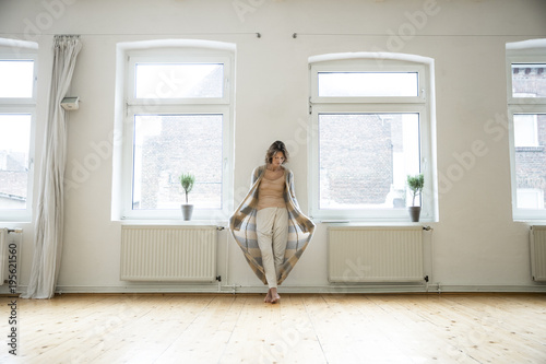 Mature woman in empty room standing at the window