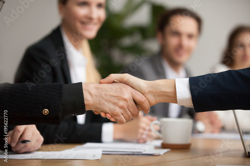 Foto  Hands of senior and young businessmen shaking at group meeting, two partners of