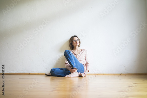 Mature woman sitting on floor in empty room thinking