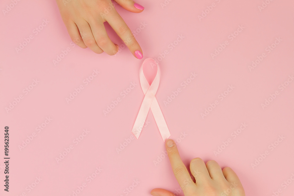 Fototapeta Women's hands with pink tape as symbol of women illness mammary cancer isolated on pink background