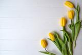 Fototapeta Tulipany - Yellow tulips on a white wooden background.