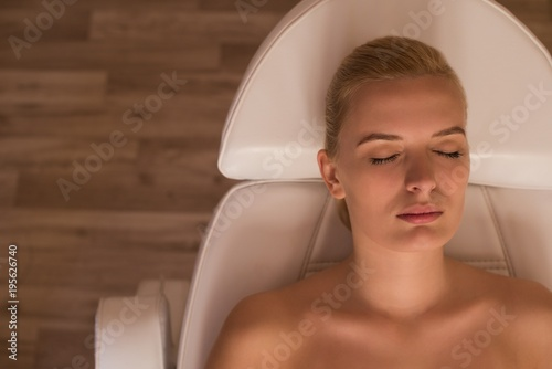 Woman getting beauty treatments while lying on  salon bed Poster