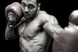 Powerful boxer punching in front of black background