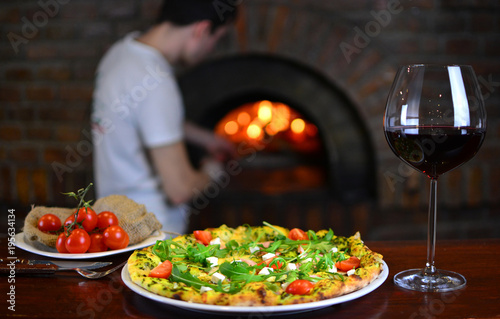 Wineglass with a red wine and tasty pizza in a pizzeria restaurant. Chef cooks pizza in a fire stone stove on a background.