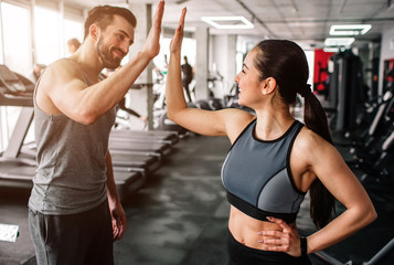 Fototapeta na wymiar A beautiful girl and her well-built boyfriend are greeting each other with a high-five. They are happy to see each othr in the gym. Young people are ready to start their workout.