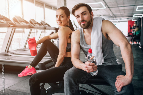 Spoed Foto op Canvas Fitness Close up of a beautiful couple sitting on the sport bench and posing. Also they are drinking water from their bottles and having rest after hard workout.