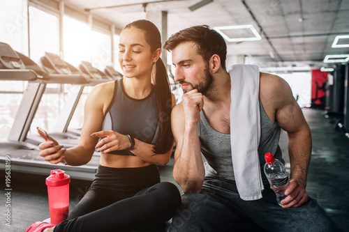 Spoed Foto op Canvas Fitness Close up of a girl sitting on the sport bench and showing something on the phone to her sport partnet, who is sitting besides her. He looks tired and bored, but she is happy.