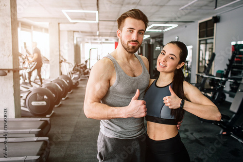 Spoed Foto op Canvas Fitness A picture of a couple standing in the sport club's training room together and showing their big thumb's up. They are happy to exsercise in this fitness club. Young couple is smiling.