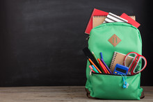 Education Concept - School Backpack With Books And Other Supplies, Blackboard Background