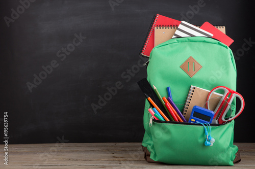 Education concept - school backpack with books and other supplies, blackboard ba Canvas Print