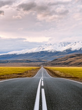 Inspirational Travel And Adventure Photography. Straight Paved Road With White Surface Markings Goes Through The Snow Capped Mountains Of Altai Republic, Russia Just Before The Sunset.