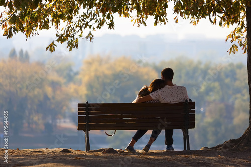 Young couple sitting on a wooden bench under a tree Fototapet