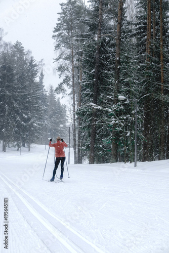 Foto op Canvas Wintersporten Young adult Caucasian female practising cross-country skiing on a scenic forest trail