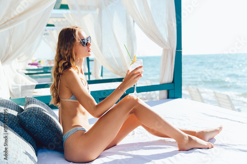 Amazing young woman in sunglasses and swimsuit holds a glass of cocktail, looking at the sea, dreaming, while relaxing on luxury sunbed Poster Mural XXL